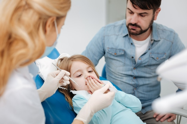 Beau dentiste pédiatrique de premier plan voulant faire une injection et effrayer involontairement son petit patient avec une seringue