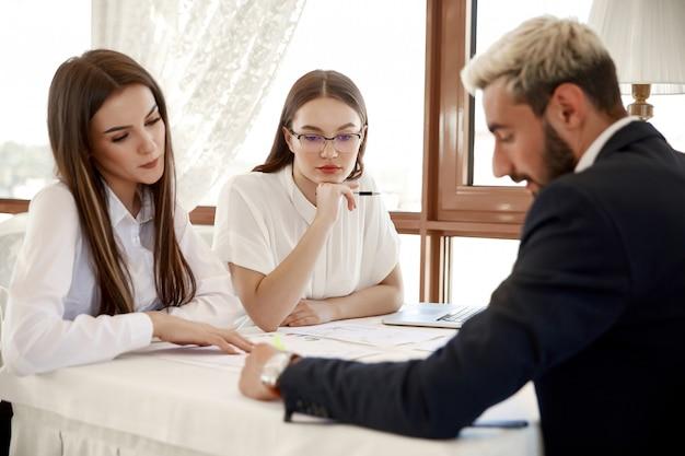 Beau directeur instruit ses assistants sur les règles de travail de l'entreprise