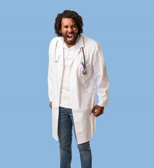 Beau docteur afro-américain hurlant de colère, expression de folie