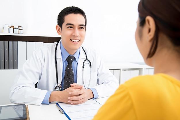 Beau docteur asiatique partageant des informations avec le patient
