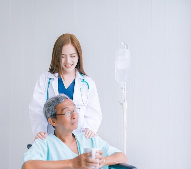 Beau docteur asiatique prenant soin d'un patient senior en fauteuil roulant