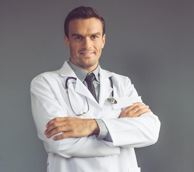 Beau docteur en blouse blanche regarde la caméra.