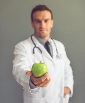 Beau docteur en blouse blanche tient une pomme. concept de régime