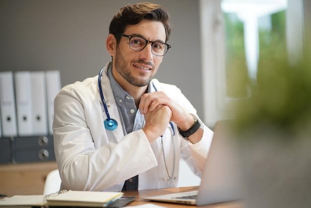 Beau docteur en blouse de laboratoire au bureau