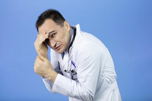 Beau docteur se cachant avec la main sur le front, choqué par le visage honteux