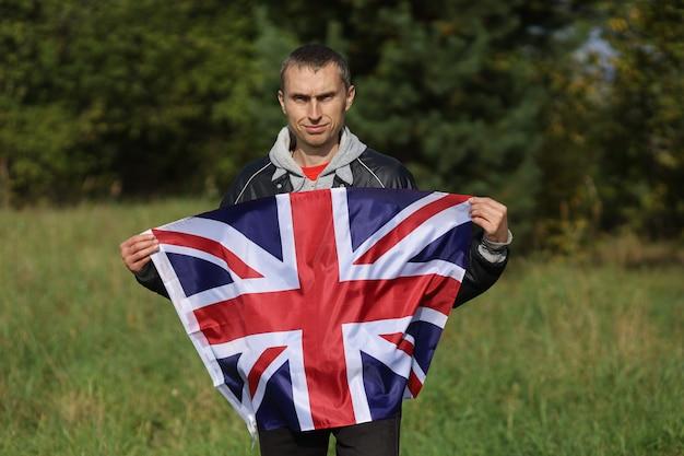 Beau drapeau de la grande-bretagne entre les mains d'un homme
