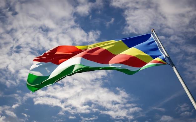 Beau drapeau national des seychelles flottant sur le ciel bleu