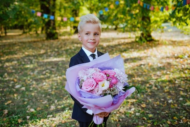 Beau écolier blond dans un uniforme scolaire détient un bouquet