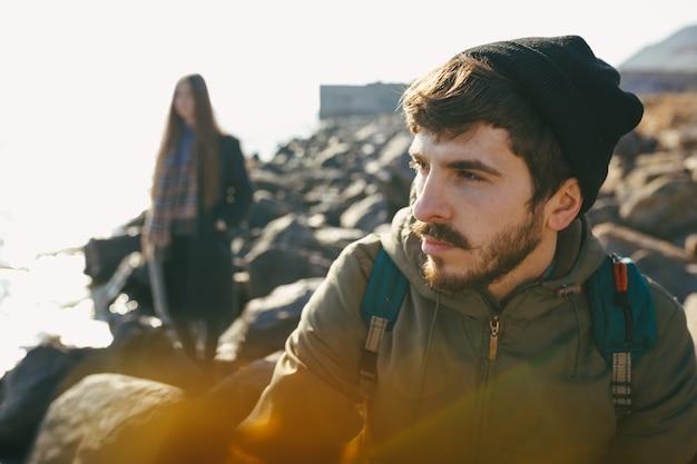 Beau et élégant couple marchant sur une plage rocheuse. couple vêtu de vestes, chapeaux et bottes. close up portrait d'humeur