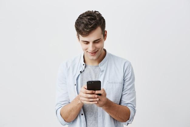 Beau étudiant joyeux aux cheveux noirs portant une chemise bleue, taper un message, utiliser l'application onlipe gratuite sur son smartphone, regarder l'écran avec le sourire, poser.