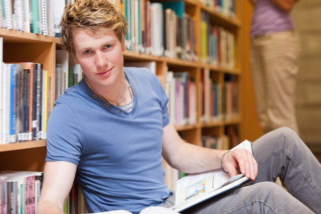 Beau étudiant posant avec un livre