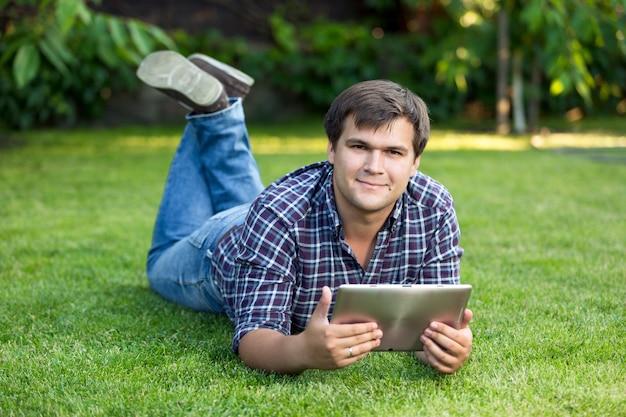 Beau étudiant souriant allongé dans le parc sur le pré avec tablette numérique