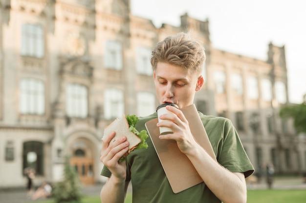 Beau étudiant universitaire mangeant un sandwich appétissant