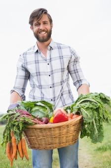 Beau fermier avec panier de légumes
