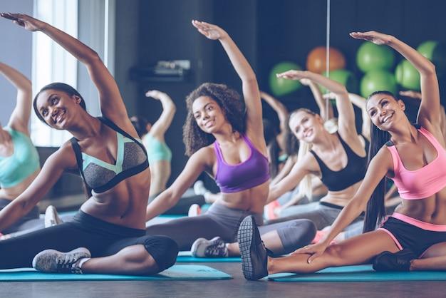 Beau et flexible. jeunes belles jeunes femmes avec des corps parfaits en vêtements de sport faisant des étirements avec le sourire au gymnase