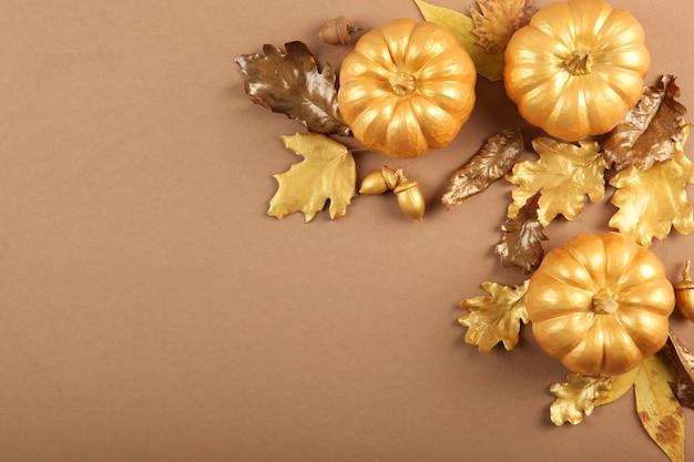 Beau fond d'automne élégant avec des feuilles d'or et vue de dessus de citrouilles