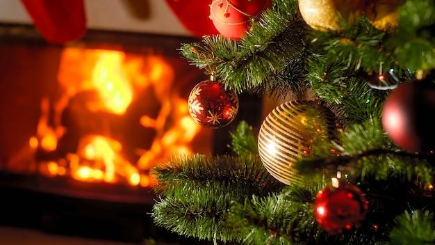 Beau fond de cheminée brûlante et arbre de noël décoré avec des boules et des guirlandes