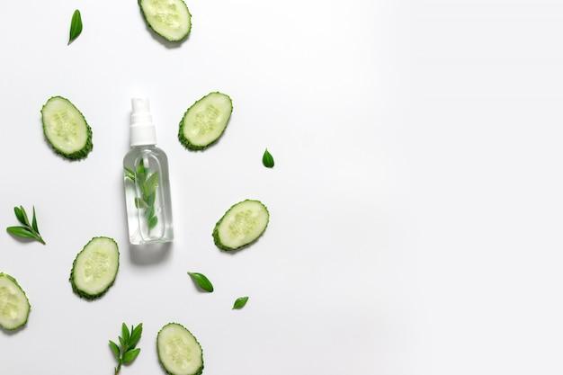 Beau fond de concombre horizontal avec une lotion liquide naturelle au concombre sur fond blanc. mise à plat, vue de dessus, espace copie