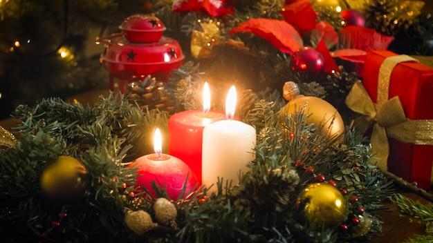Beau fond de noël avec des bougies rougeoyantes, des coffrets cadeaux et une couronne sur une table décorée
