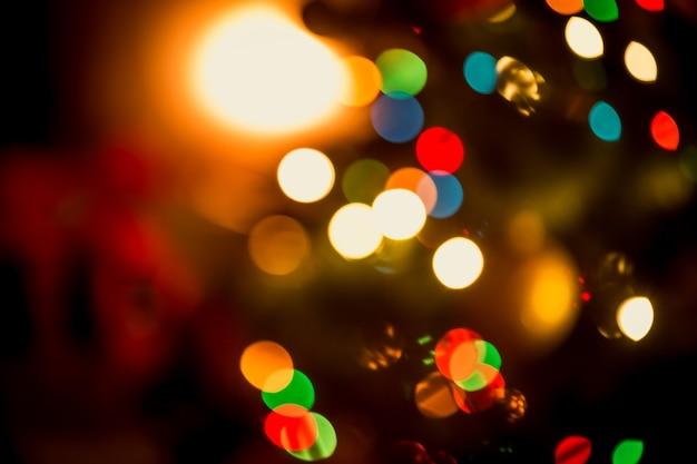Beau fond de noël avec des lumières colorées rougeoyantes floues