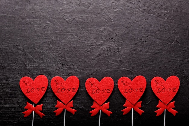 Beau fond de saint valentin avec des coeurs rouges sur fond noir. carte pour la saint-valentin. concept d'amour.