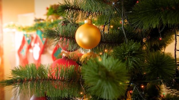 Beau fond de vacances d'hiver avec arbre de noël décoré dans le salon, cheminée avec chaussettes pour cadeaux et boules dorées sur branche de sapin