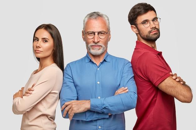Beau frère, soeur et leur père âgé posant contre le mur blanc