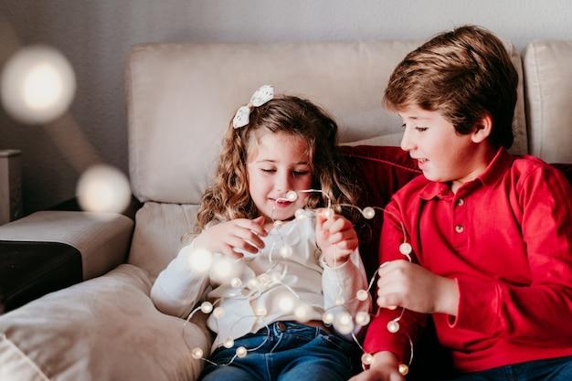 Beau frère et soeur à la maison en jouant avec guirlande de lumières