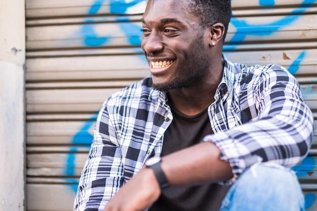 Beau gai beau jeune homme noir afro-américain souriant et s'amusant tout en s'asseyant et se relaxant dans la ville avec un fond urbain