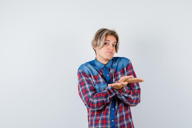 Beau garçon adolescent en chemise à carreaux montrant un geste impuissant et hésitant, vue de face.