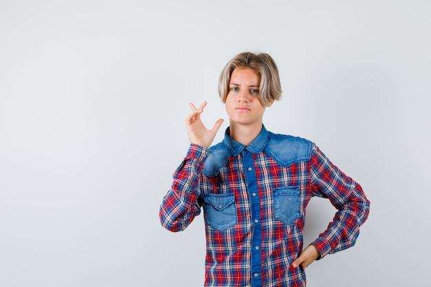 Beau garçon adolescent en chemise à carreaux pointant vers le coin supérieur gauche et l'air réfléchi, vue de face.