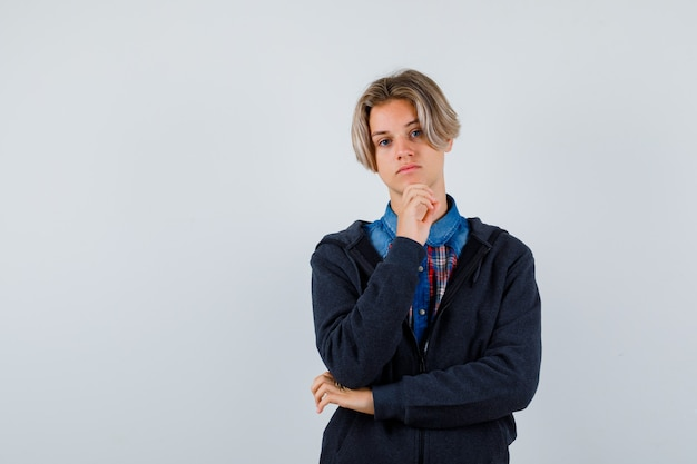 Beau garçon adolescent en chemise, sweat à capuche soutenant le menton à portée de main et l'air sombre, vue de face.