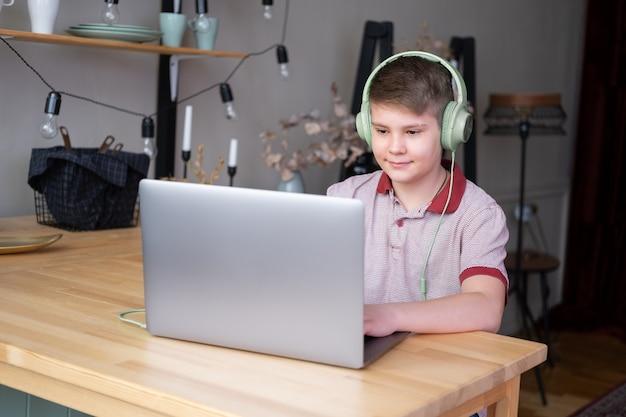 Beau garçon adolescent dans des écouteurs étudiant en ligne, jouant à des jeux vidéo à l'aide d'un ordinateur portable assis sur la cuisine.