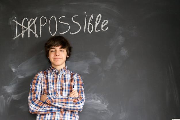 Beau garçon adolescent debout sous le mot impossible est devenu possible sur tableau noir