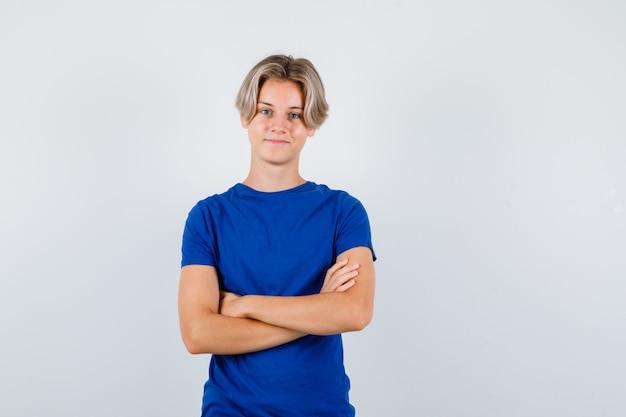 Beau garçon adolescent gardant les bras croisés en t-shirt bleu et l'air joyeux. vue de face.