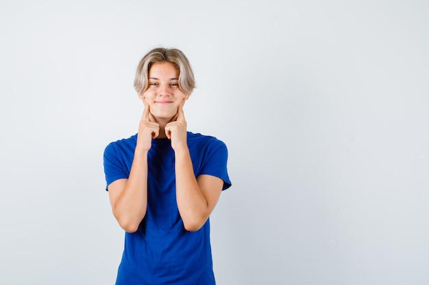 Beau garçon adolescent gardant les doigts sur les joues en t-shirt bleu et l'air joyeux, vue de face.