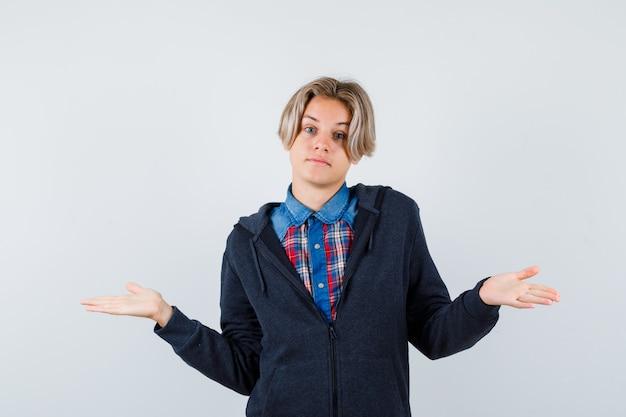 Beau garçon adolescent montrant un geste impuissant en chemise, sweat à capuche et semblant confus. vue de face.