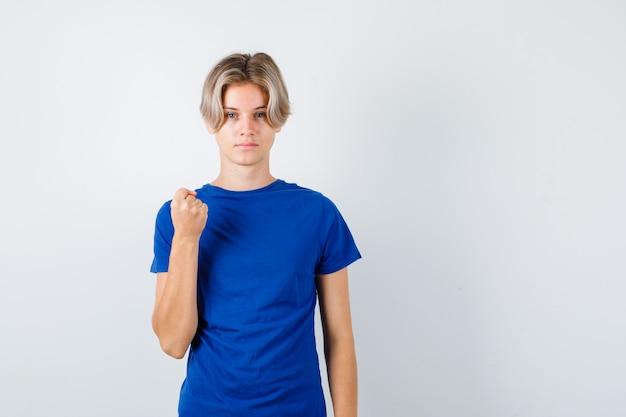 Beau garçon adolescent montrant le poing fermé en t-shirt bleu et l'air fier. vue de face.