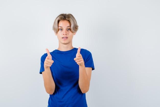 Beau garçon adolescent pointant vers l'avant en t-shirt bleu et l'air perplexe, vue de face.