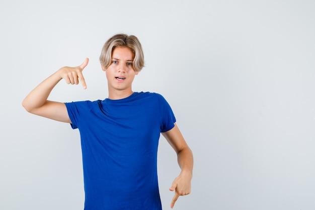 Beau garçon adolescent pointant vers le bas en t-shirt bleu et l'air confiant, vue de face.