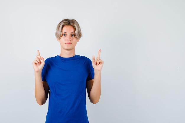 Beau garçon adolescent pointant vers le haut en t-shirt bleu et l'air intelligent. vue de face.