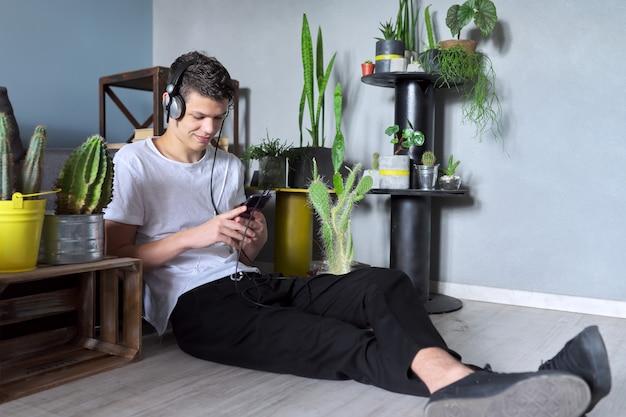 Beau garçon adolescent souriant dans des écouteurs avec smartphone assis à la maison, écoutant un livre de blog audio de musique, se reposant, jouant, faisant des études. concept d'adolescents de mode de vie de loisirs d'éducation