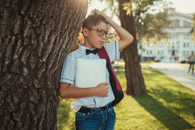 Un beau garçon d'âge scolaire est debout près d'un arbre et tient une tablette. l'écolier est vêtu d'un jean et d'un torse nu avec un noeud papillon.
