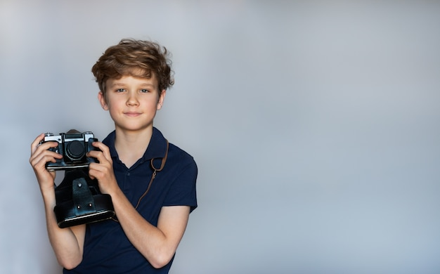 Beau garçon avec un appareil photo argentique debout sur un fond gris-bleu