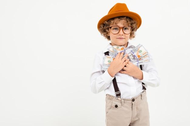 Beau garçon aux cheveux bouclés en chemise blanche, chapeau brun, lunettes à bretelles noires détient de l'argent isolé sur blanc