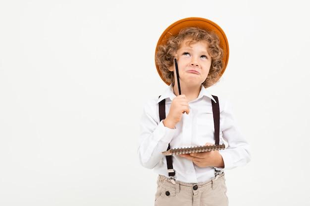 Beau garçon aux cheveux bouclés en chemise blanche, chapeau brun, lunettes à bretelles noires écrit en note et pense isolé sur blanc