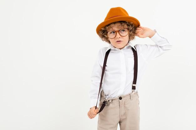 Beau garçon aux cheveux bouclés en chemise blanche, chapeau brun, verres à bretelles noires se dresse isolé sur blanc