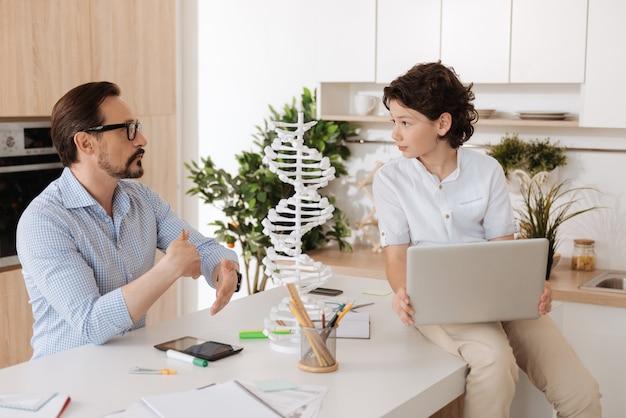 Beau garçon aux cheveux noirs assis sur le comptoir de la cuisine avec un ordinateur portable sur ses genoux et prêtant attention à chaque mot que son père dit