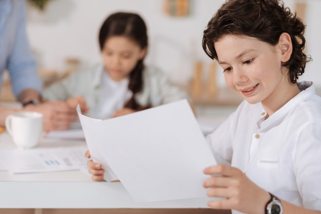 Beau garçon aux cheveux ondulés tenant deux feuilles de papier et lisant d'eux tout en ayant l'air heureux et intéressé par leur contenu