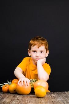 Un beau garçon aux cheveux rouges agréable avec pamplemousse d'agrumes